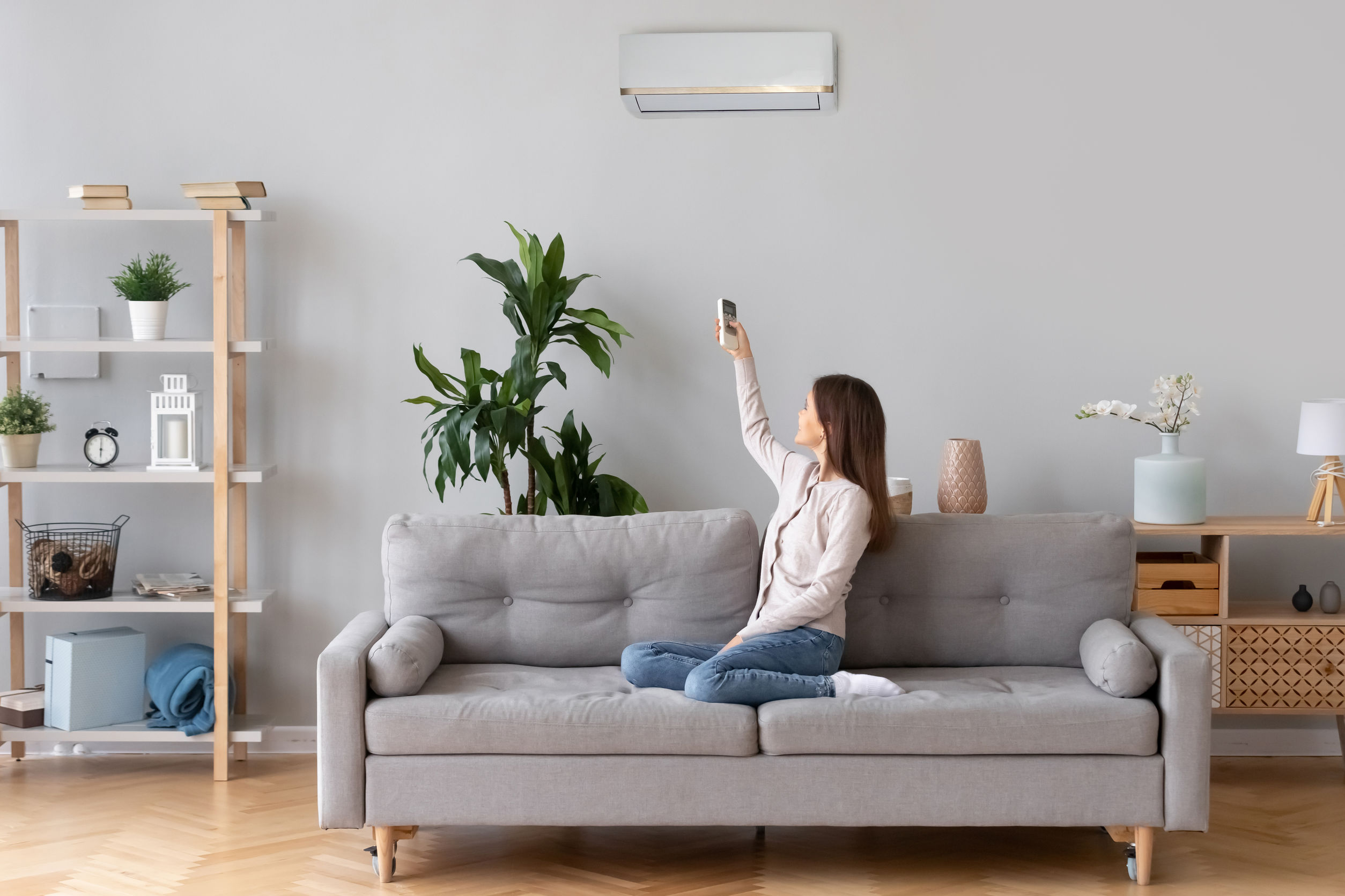 Young happy woman switching on air conditioner sitting on couch at convenient cozy home, lady relaxing on sofa in living room holding remote climate control to cooler system set comfort temperature